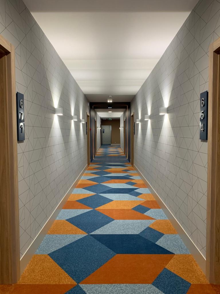 Hotel Európa fit apartman közlekedő részlet, szintenként változó színű szobaszámokkal